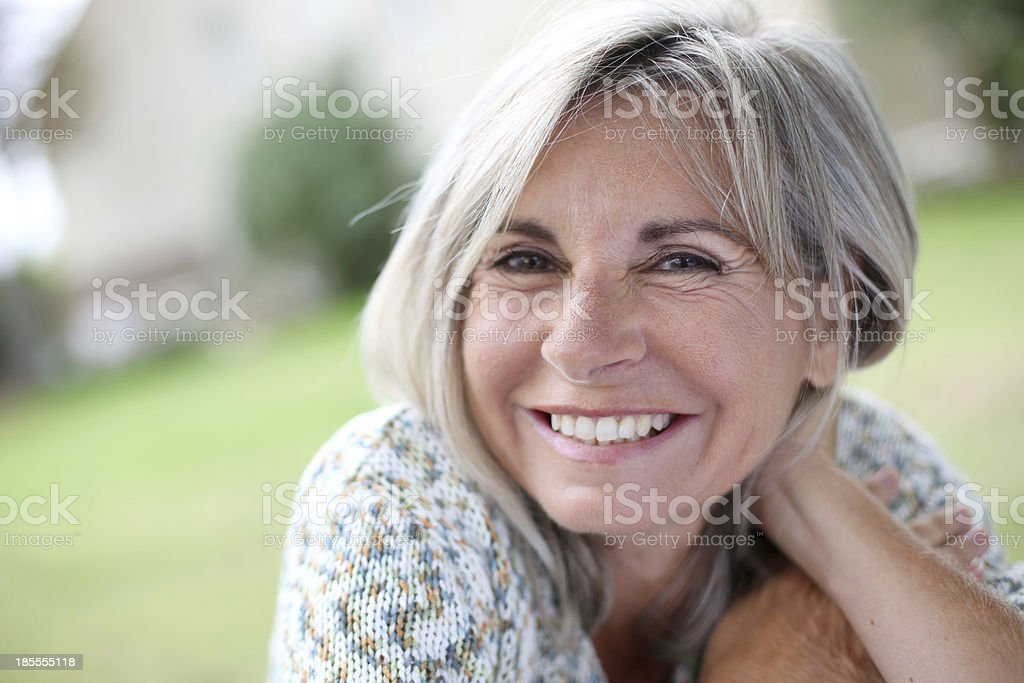 Closeup of laughing blonde senior woman standing in garden stock photo