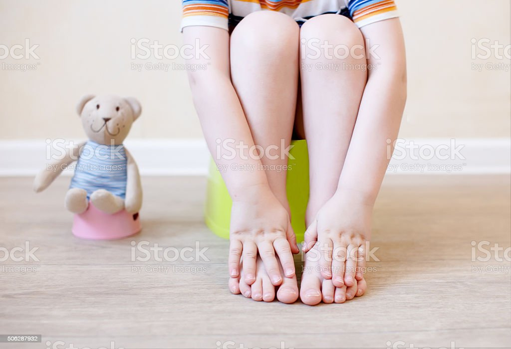close-up of legs of the child sitting on the potty stock photo