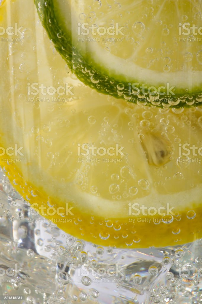 Closeup of Lemon and Lime Slices with Bubbles in Soda Water with Ice Cubes stock photo
