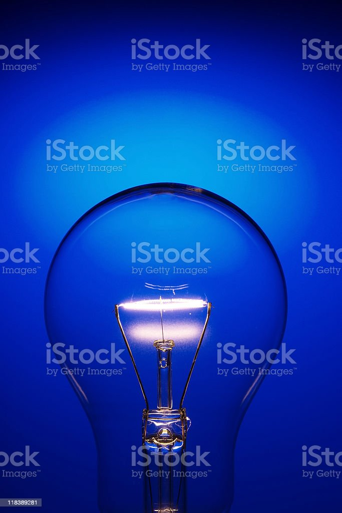 Close-up of light bulb against blue background with copy space royalty-free stock photo