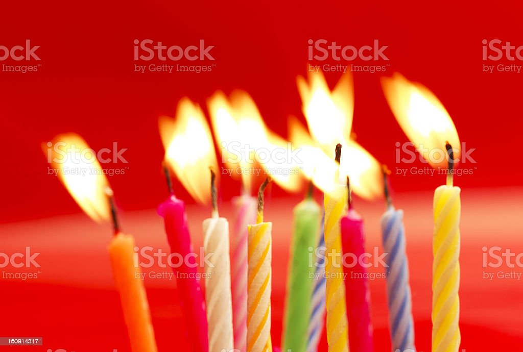 A close-up of lit birthday candles against a red background stock photo