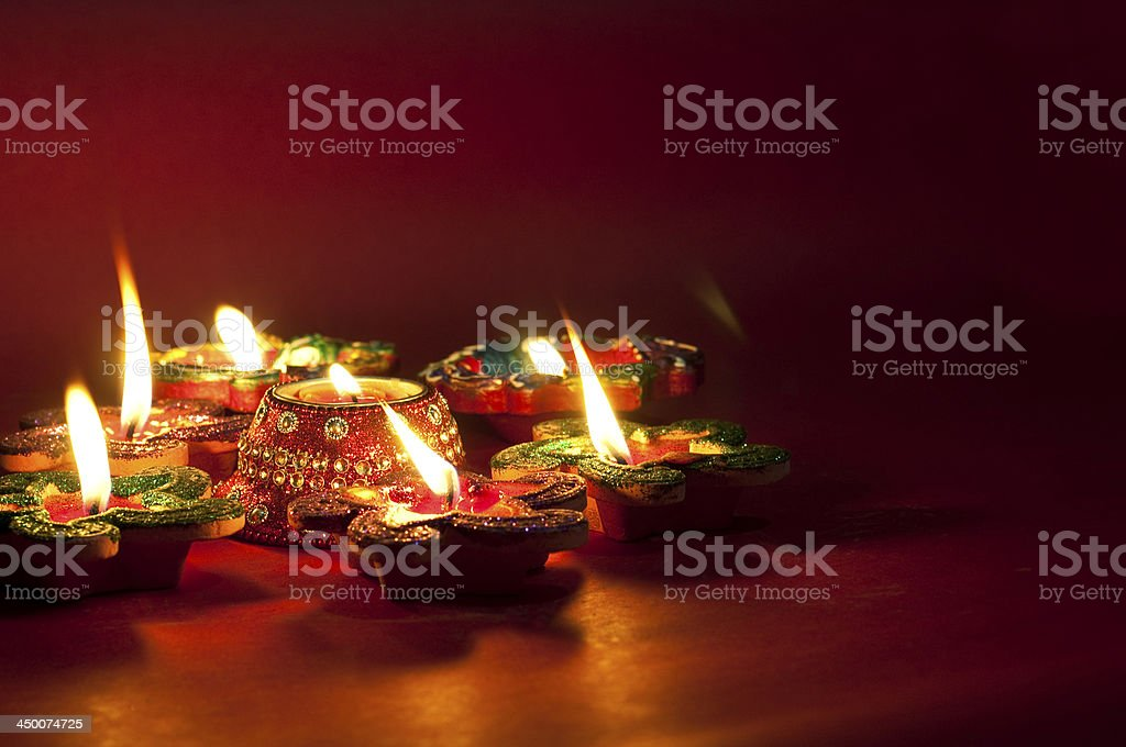 Close-up of lit colorful candles on a wooden surface stock photo
