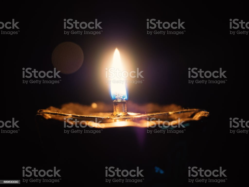 Close-up of lit oil lamp in the dark room, shallow depth of field stock photo