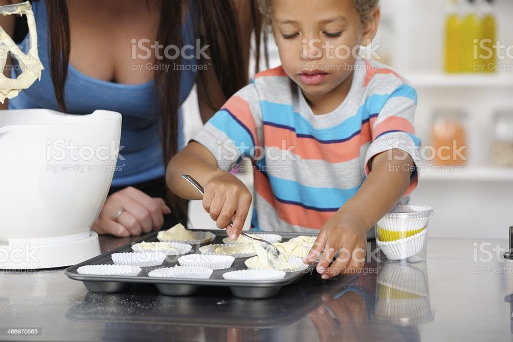 Close-up Of Little Boy Filling Muffin Cases With Cake Mixture royalty-free stock photo