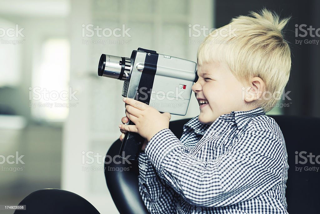 Close-up of little boy making video with vintage video royalty-free stock photo