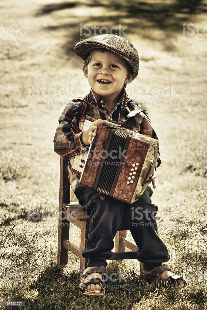 Close-up of little boy outdoors playing accordion stock photo