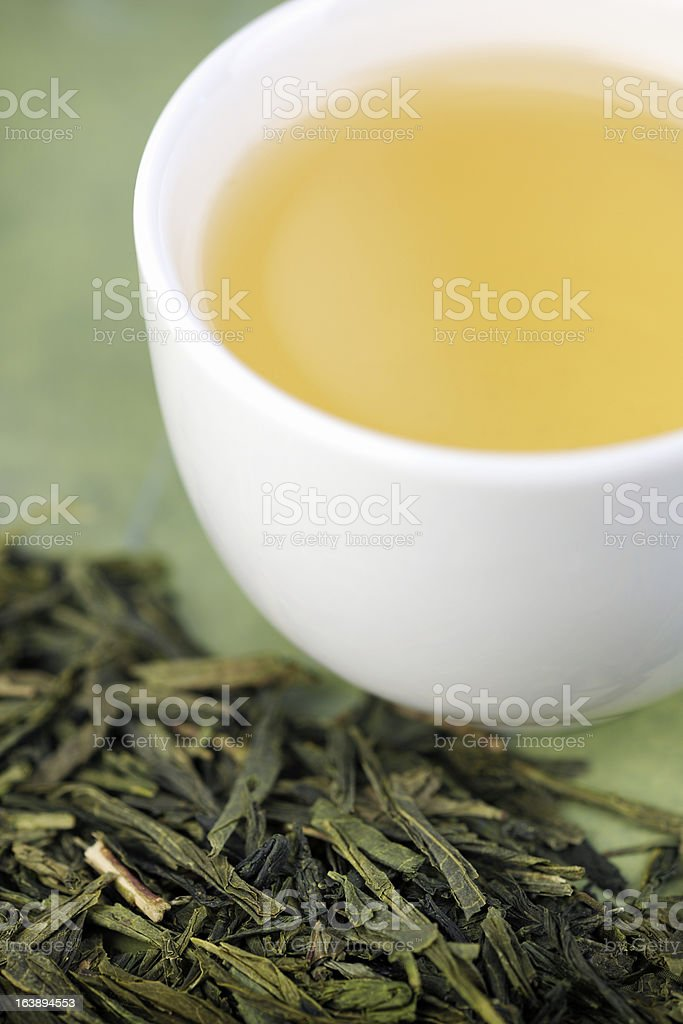 Close-up of loose green tea and cup stock photo