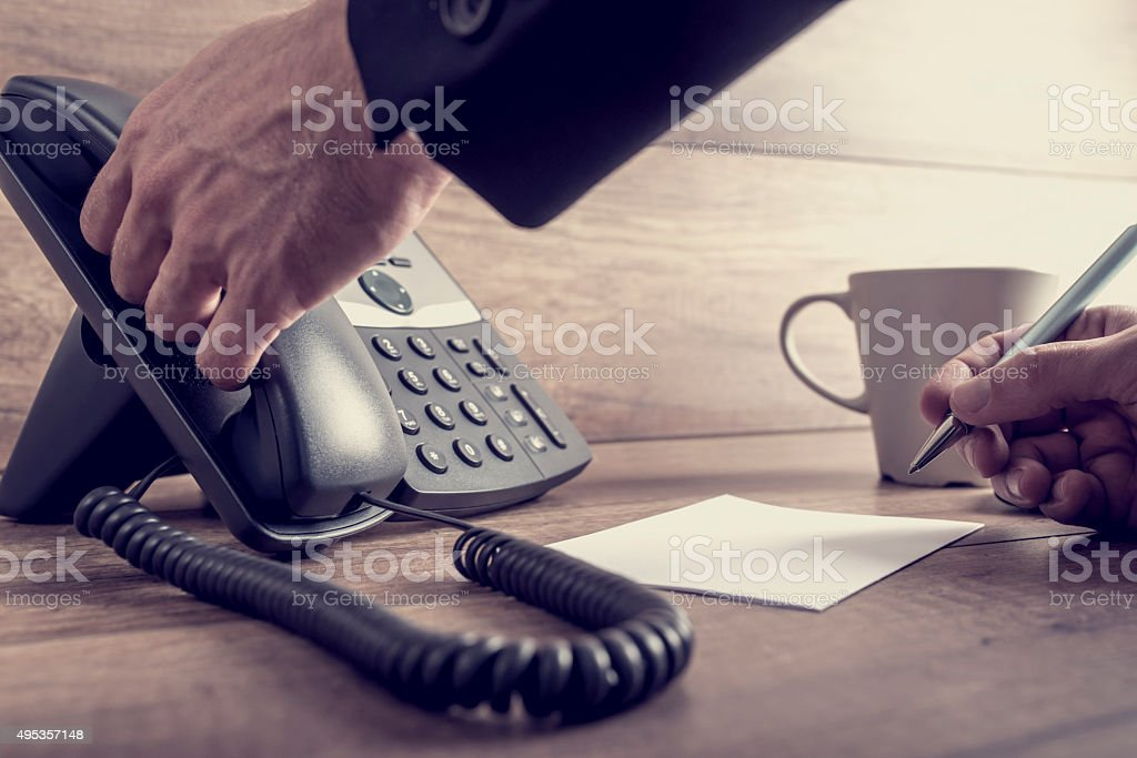 Closeup of male assistant about to answer a telephone call stock photo