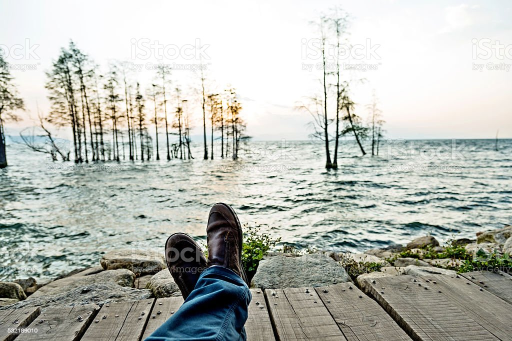 Close-up of male feet wearing shoes by the lake stock photo
