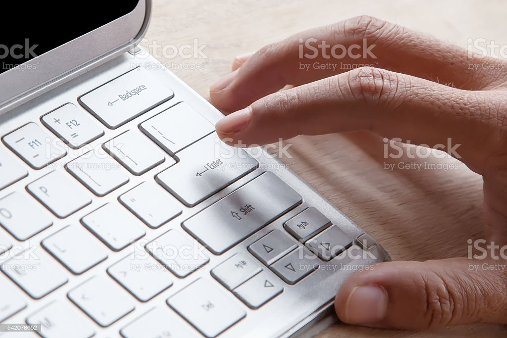 Close-up of male forefinger on keyboard on tablet computer stock photo