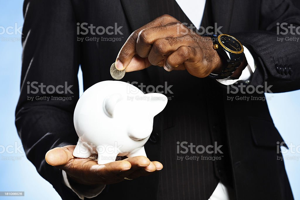 Close-up of male hand adding coin to piggybank royalty-free stock photo