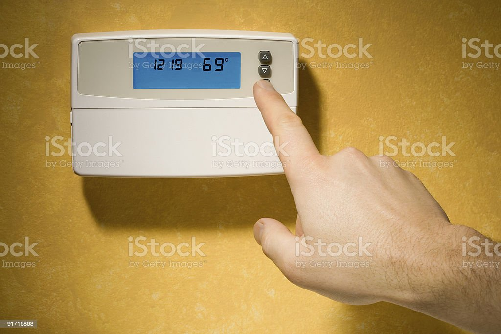 Closeup of Male Hand Adjusting The Thermostat Setting royalty-free stock photo