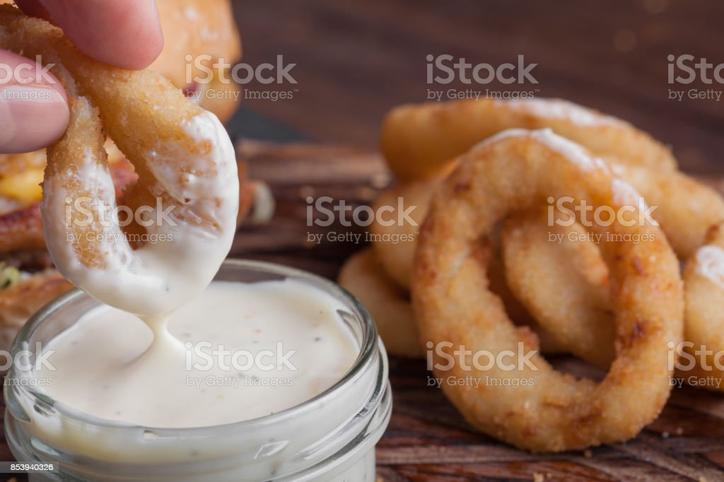 Closeup of male hand dipping in white garlic sauce fried onion rings stock photo
