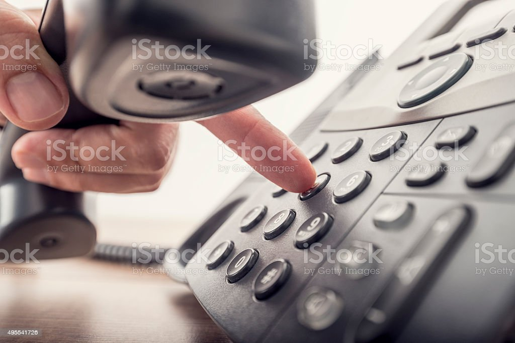 Closeup of male hand holding telephone receiver while dialing a stock photo