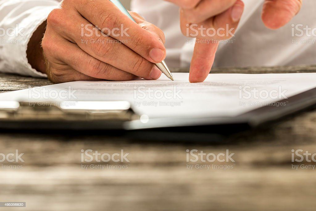 Closeup of male hand pointing where to sign a contract stock photo