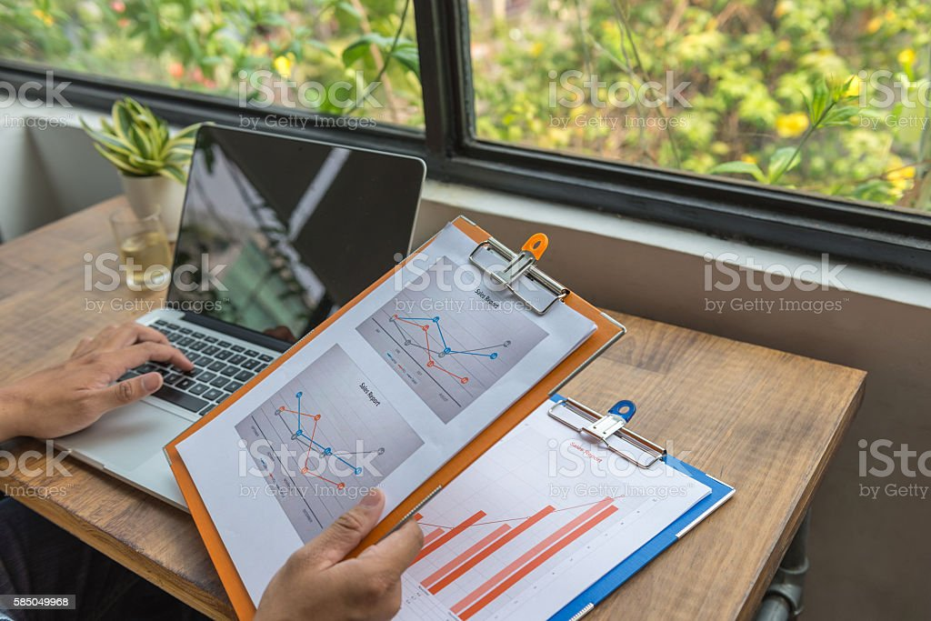 Close-up of male hand typing and carrying sales report document stock photo