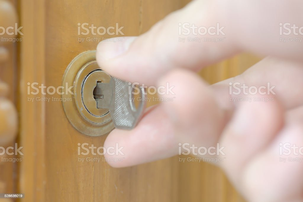 Closeup of male hand unlocking cabinet stock photo