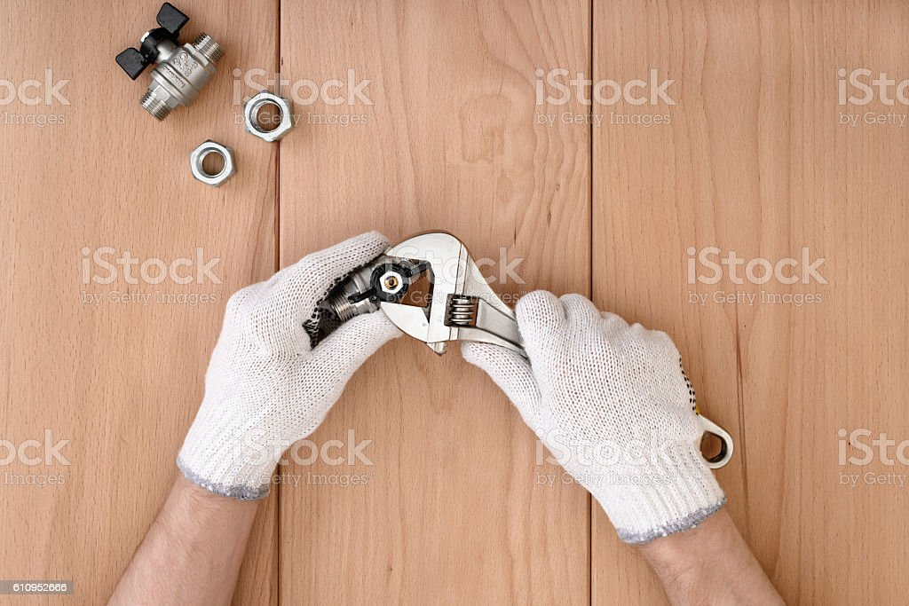 Close-up of male hands holding the ball valve and stock photo