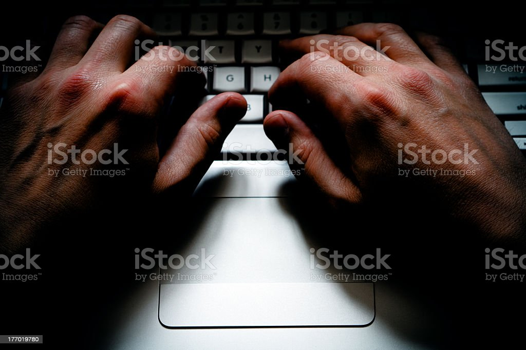 A close-up of male hands on a laptop keyboard stock photo