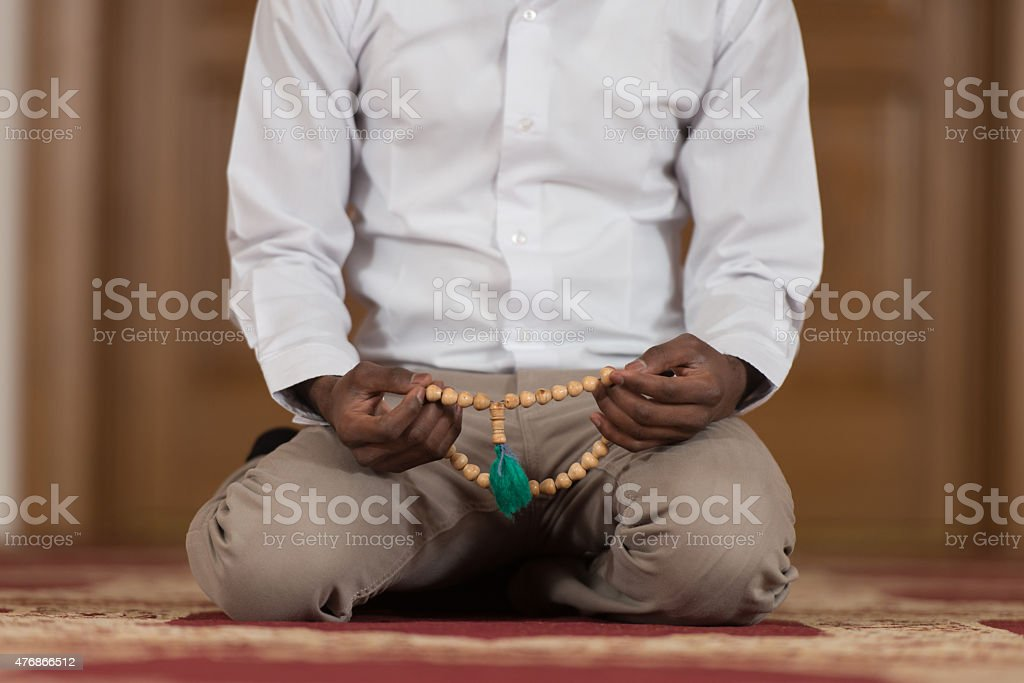 Close-Up Of Male Hands Praying With Rosary stock photo