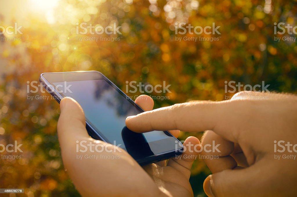 Primer plano de manos del hombre usando un teléfono inteligente, fondo de la naturaleza foto de stock libre de derechos