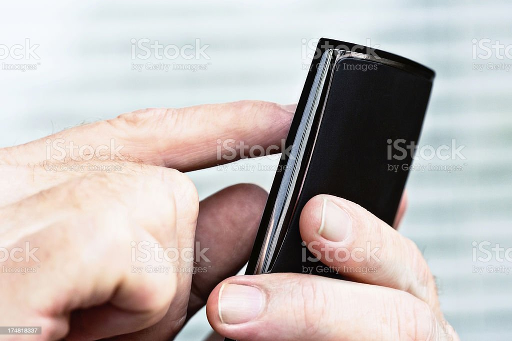 Close-up of male hands using mobile phone indoors royalty-free stock photo