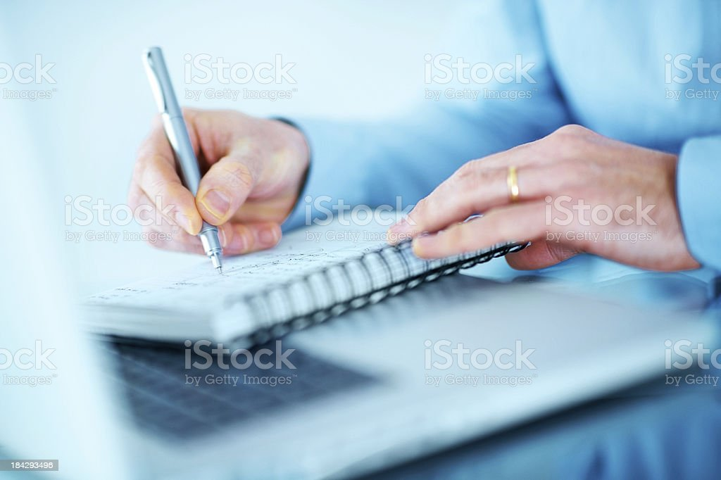 Closeup of male hands writing notes with a laptop royalty-free stock photo