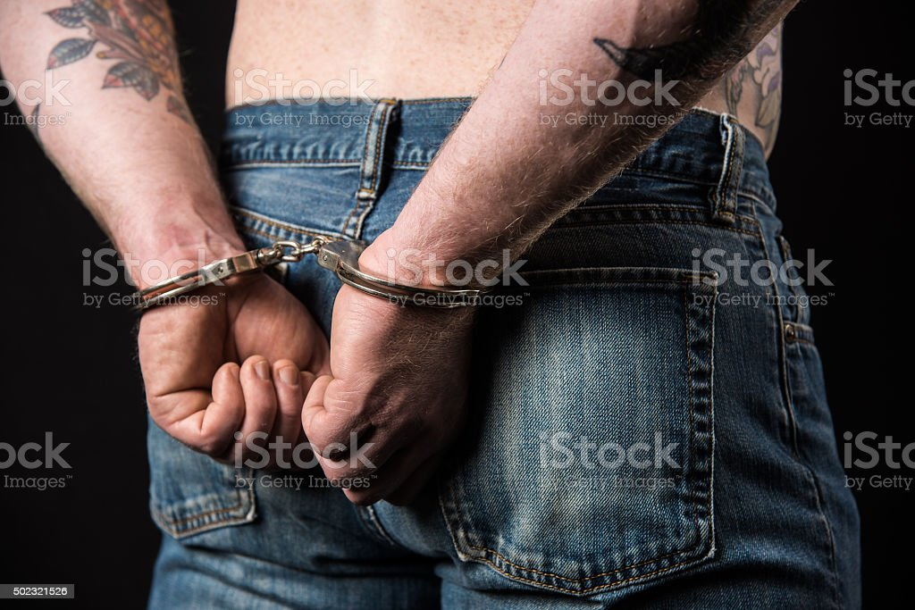 Close-Up of Male in Handcuffs Behind the Back stock photo