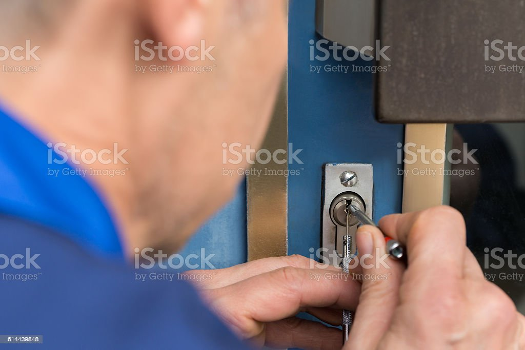 Close-up Of Male Lockpicker Fixing Door Handle At Home stock photo