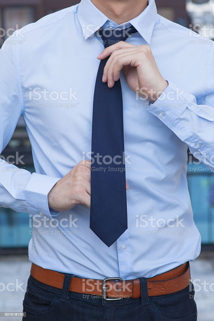 Closeup of Male office worker tying a tie stock photo