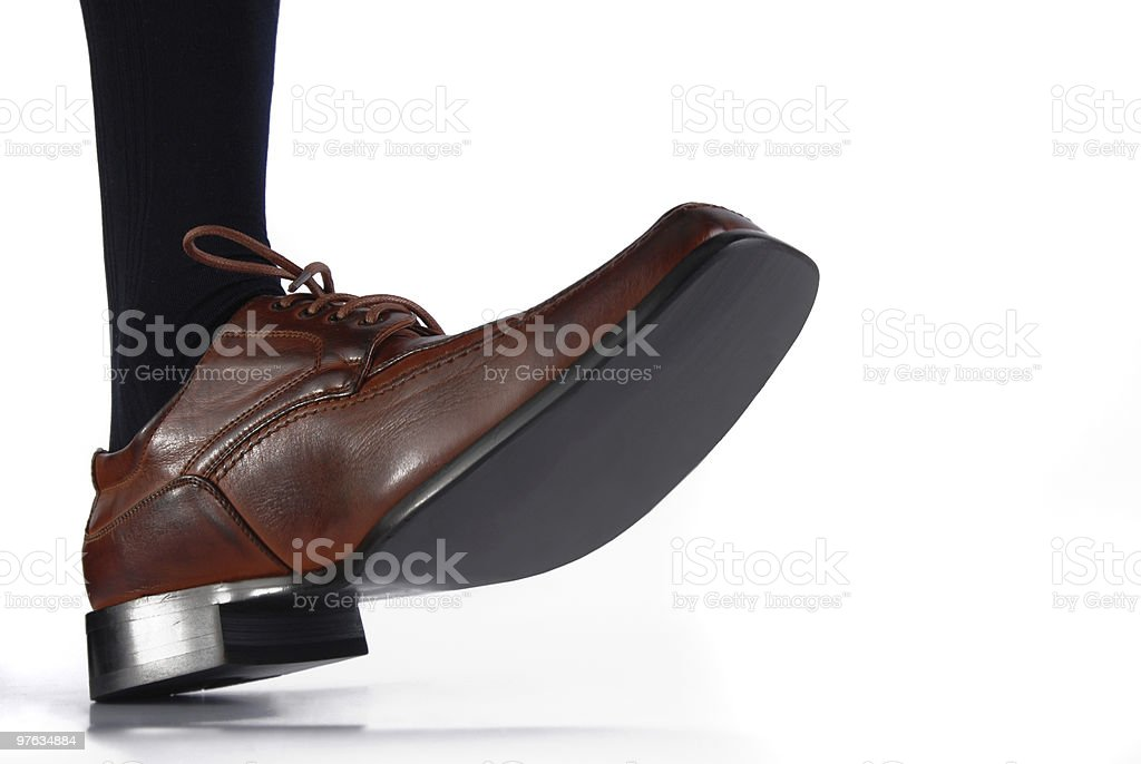 Close-up of male shoe stepping on white background royalty-free stock photo