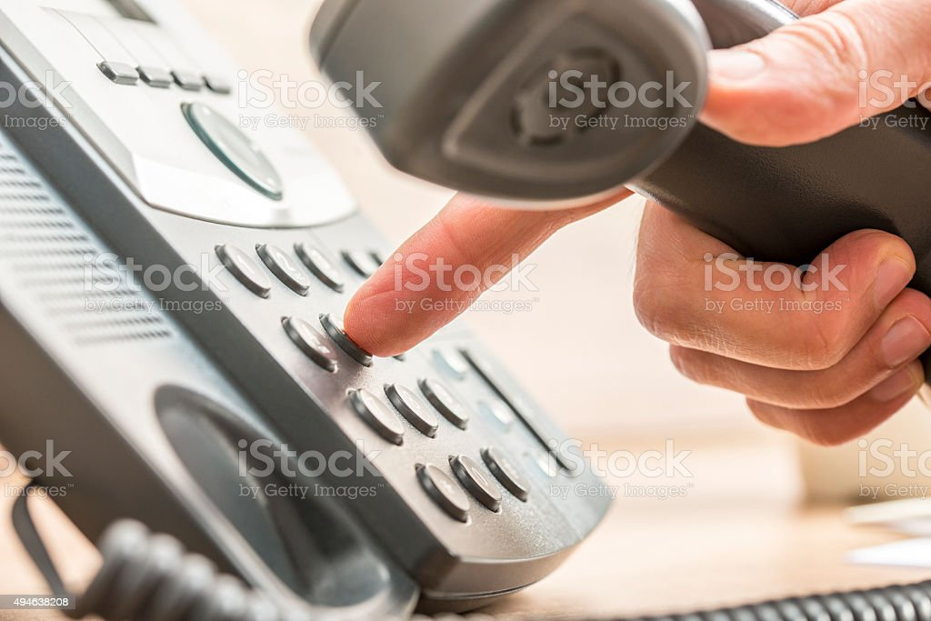 Closeup of male telemarketing salesperson holding a telephone re stock photo