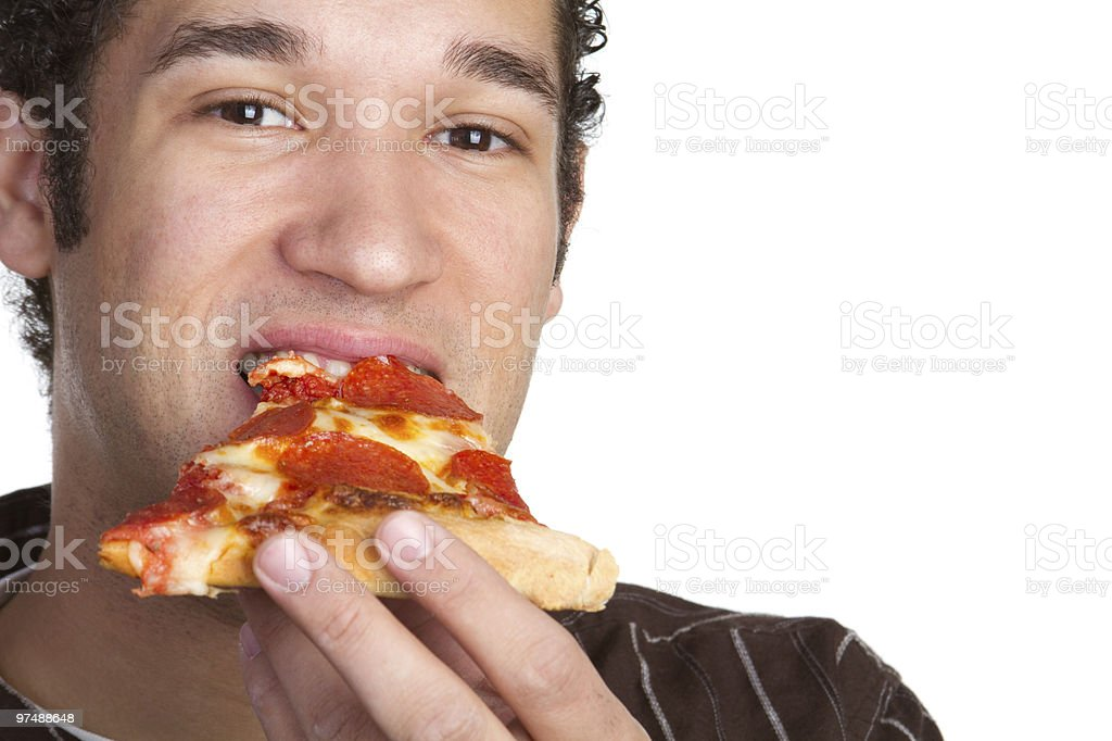 Close-up of man biting into a slice of pepperoni pizza royalty-free stock photo