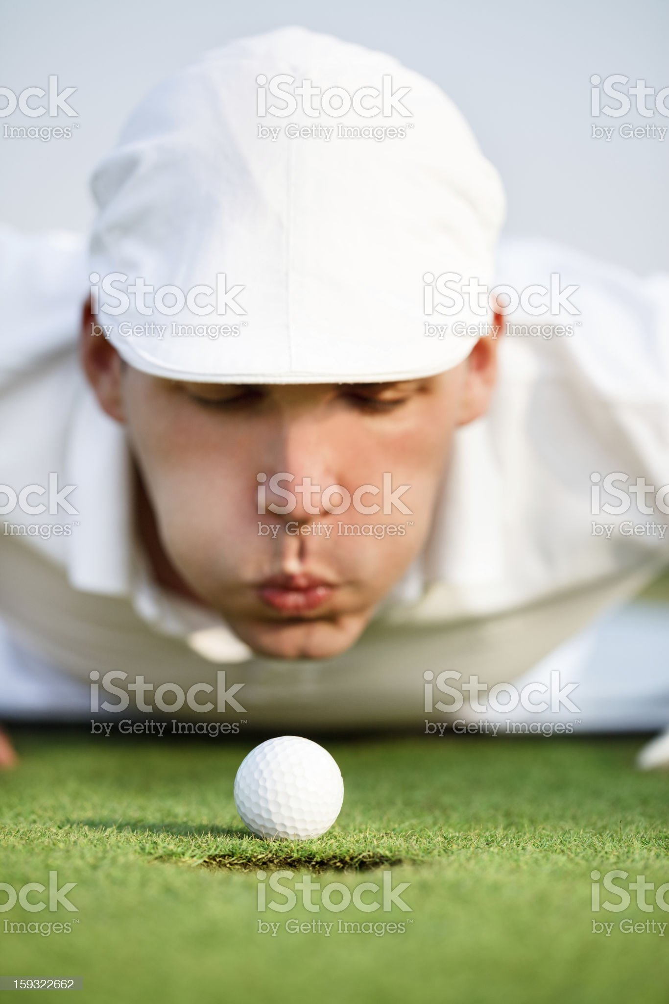 Close-up of man blowing on golf ball royalty-free stock photo