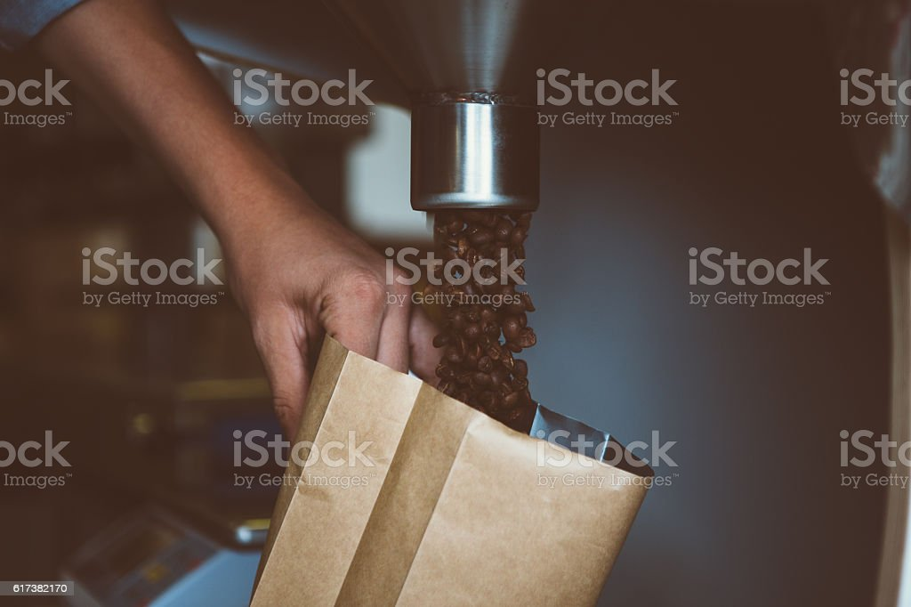 close-up of man filling package with coffee beans stock photo
