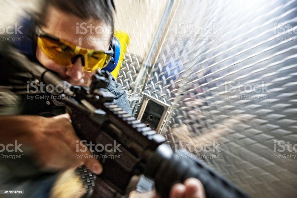 Close-up of man firing an assault rifle stock photo