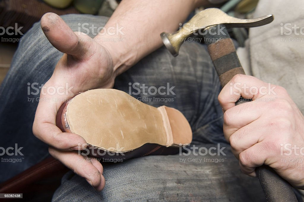 Close-up of man fixing bottom of a shoe stock photo