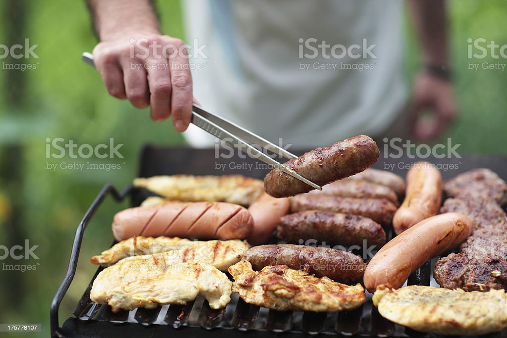 Closeup of man grilling meats during summer weekend stock photo