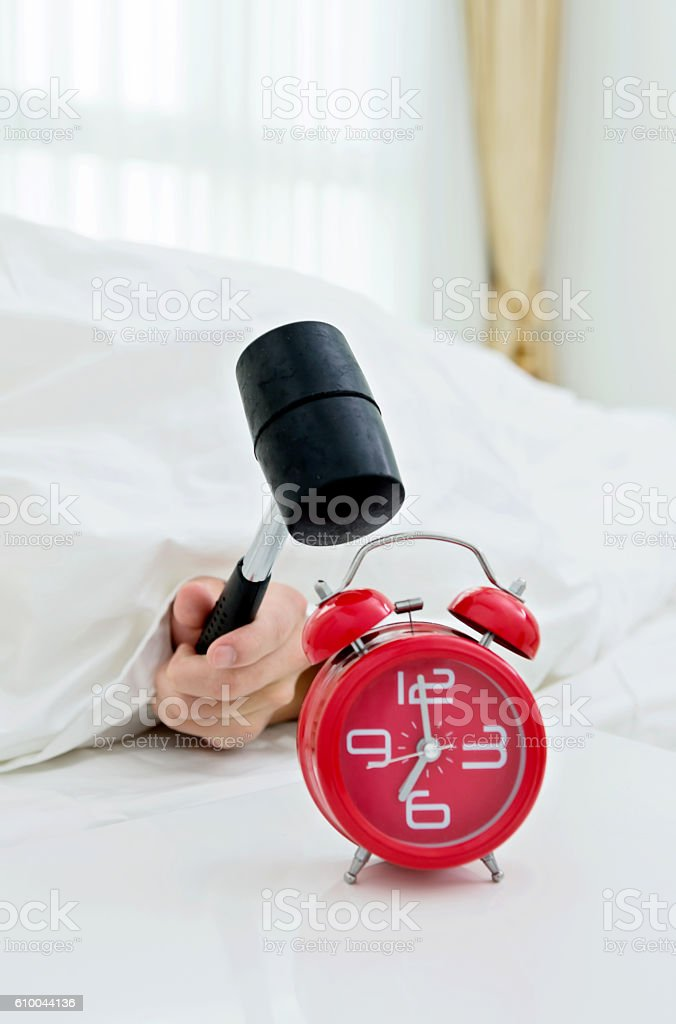 Closeup of man hitting alarm clock with hammer stock photo