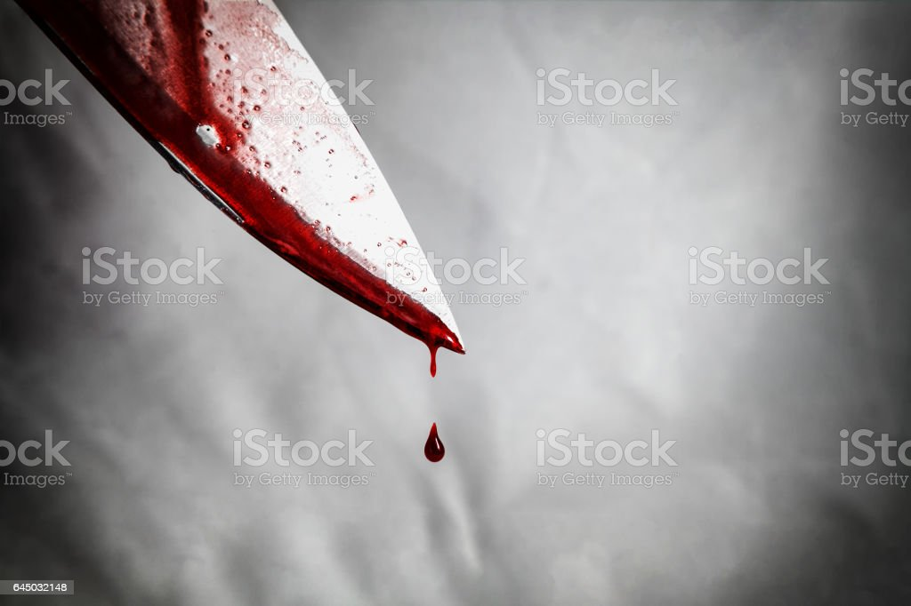 close-up of man holding knife smeared with blood and still dripping. stock photo