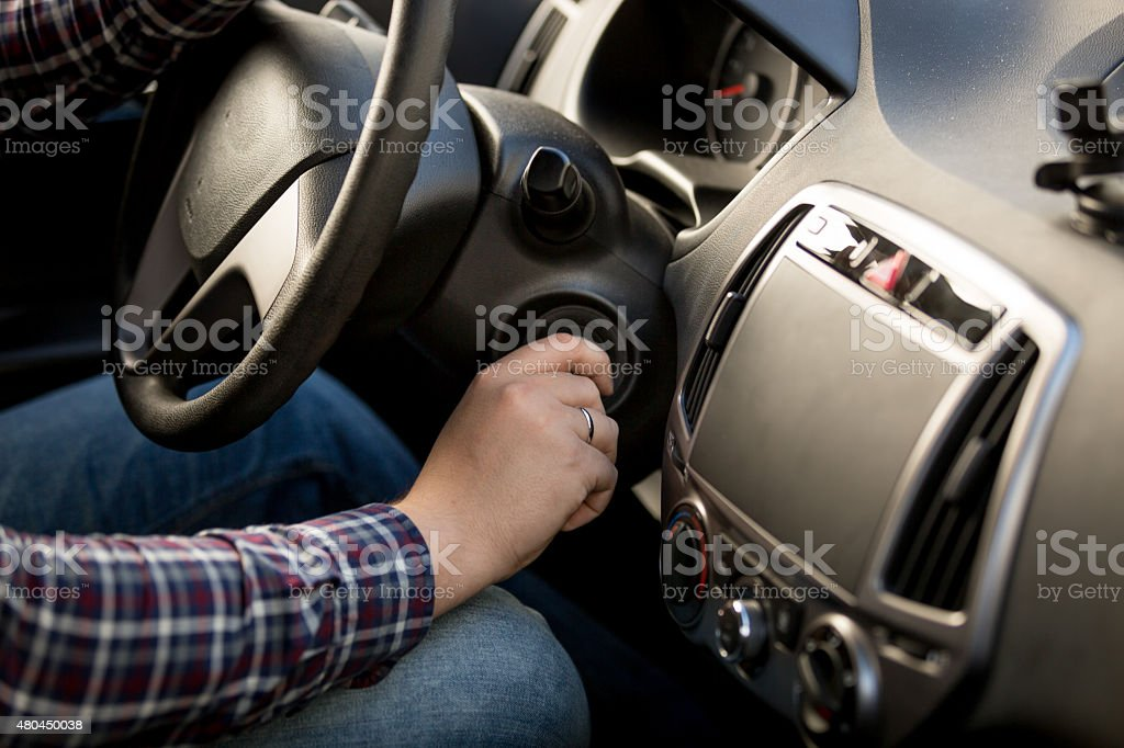 Closeup of man inserting key in car ignition lock stock photo