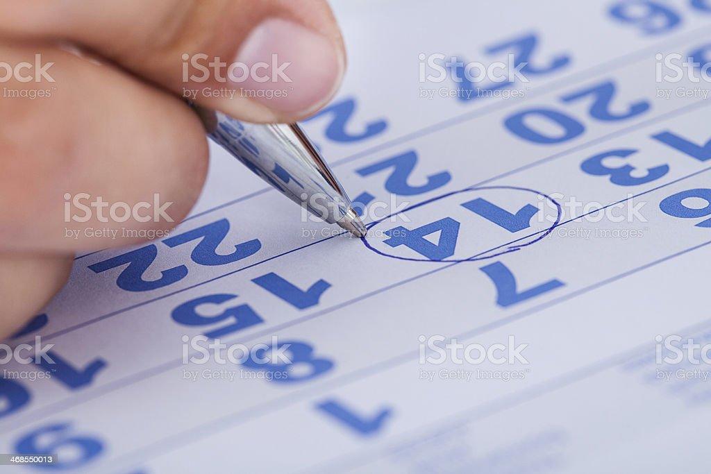 Close-up Of Man Marking On Calendar stock photo