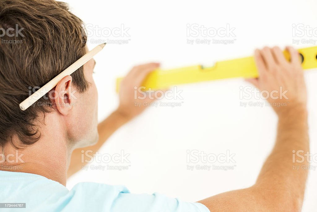 Close-Up Of Man Measuring Wall With Level stock photo