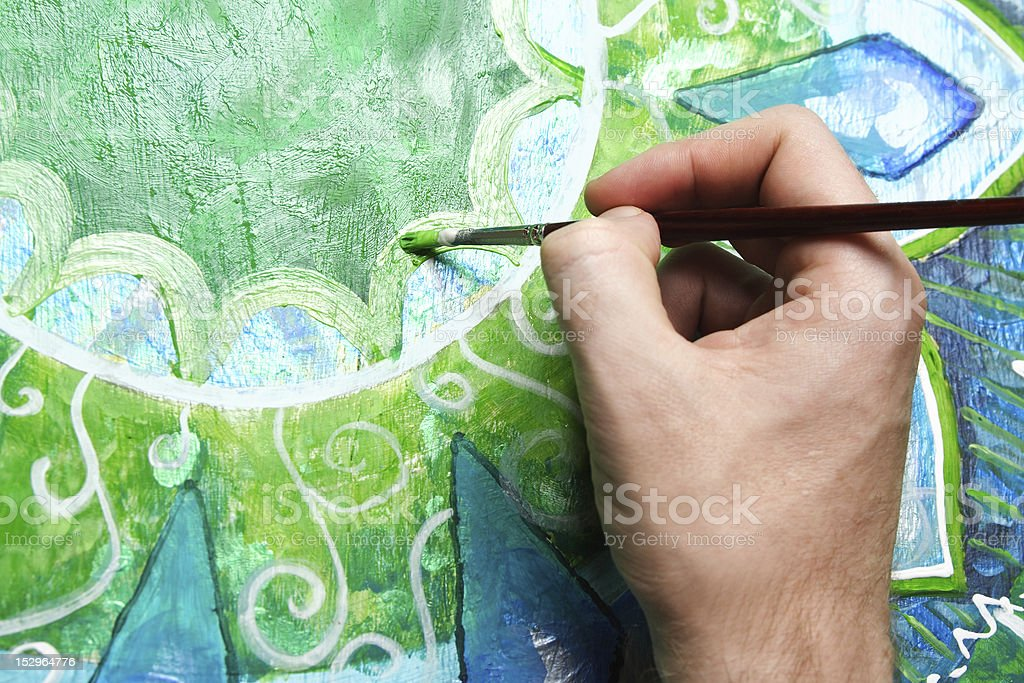 closeup of man painting green picture with circle pattern stock photo