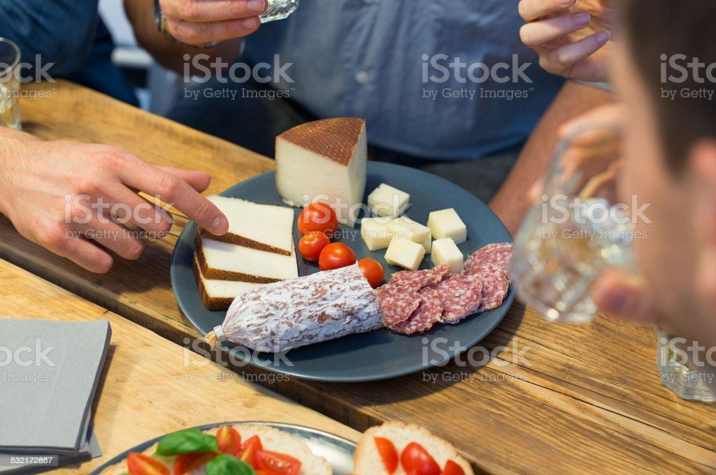 Closeup of man picking cheese slice stock photo