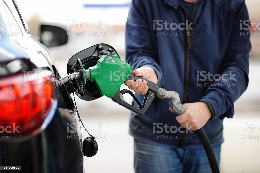 Closeup of man pumping gasoline fuel in car stock photo