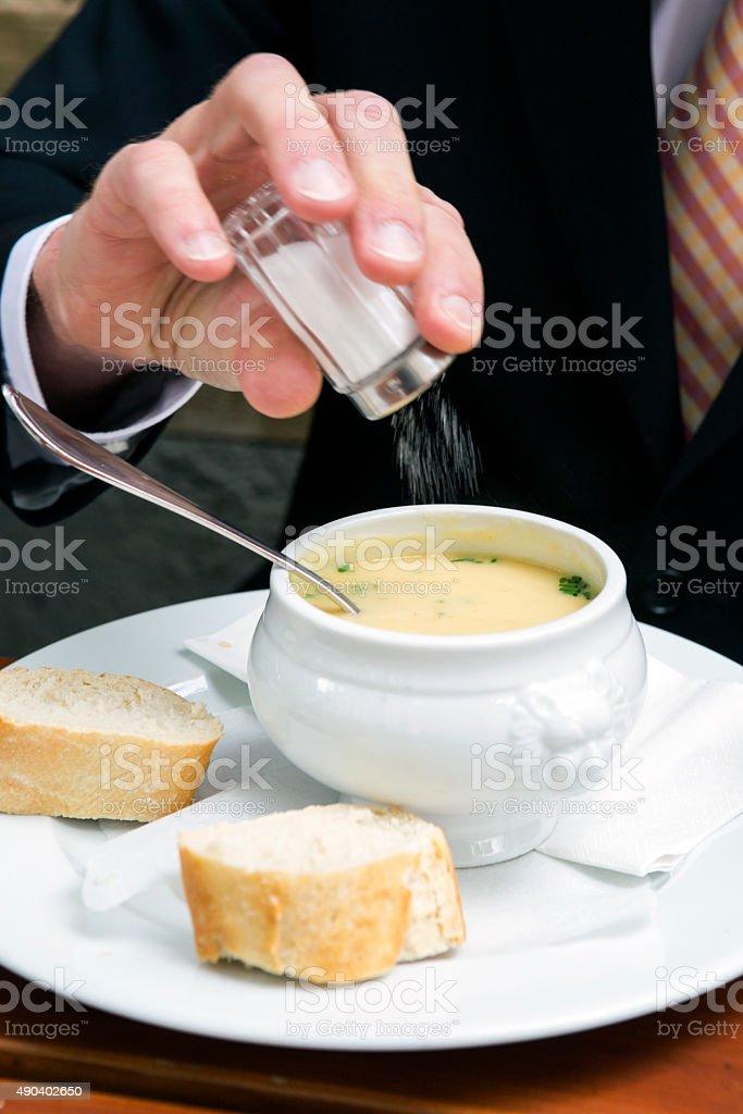 closeup of man putting salt in a bowl of soup stock photo