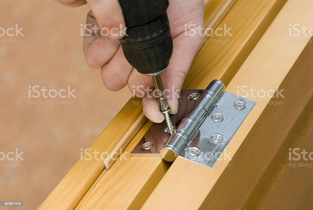 Close-up of man screwing in hinge on door jam stock photo