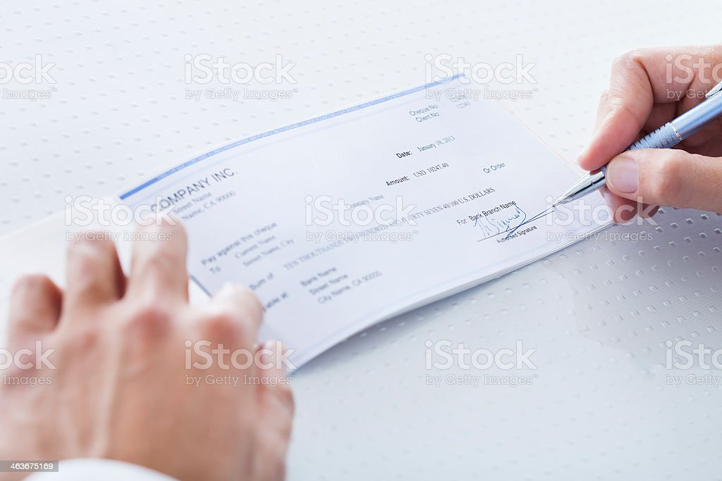 Close-up of man signing a check, hands are partially shown stock photo