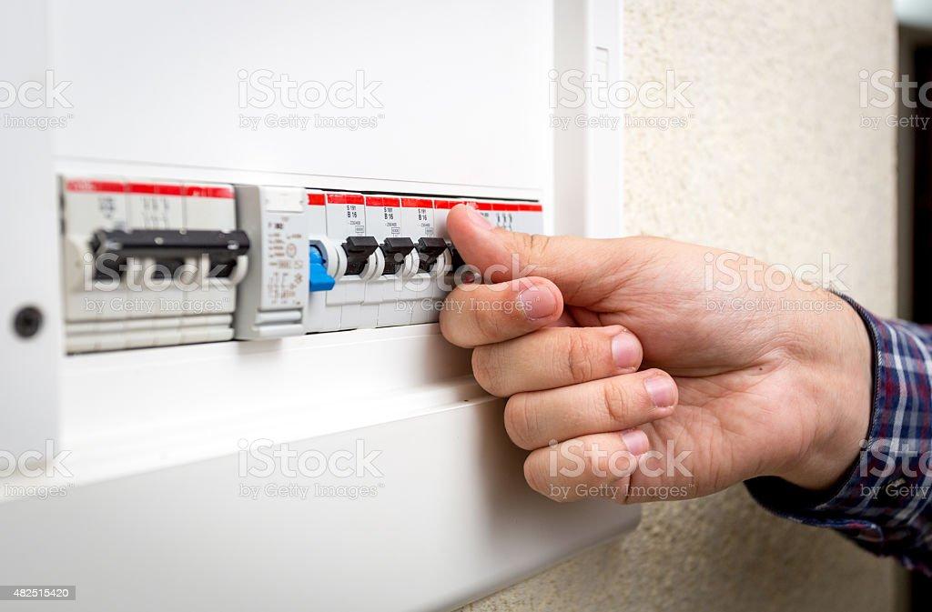 Closeup of man switching on fuseboard stock photo